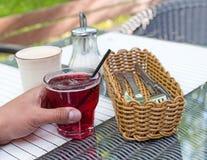 Χυμός κερασιών στο αρσενικό χέρι με το μαύρο σωλήνα, φλυτζάνι γυαλιού, καλάθι με για τα μαχαιροπήρουνα, φλυτζάνι καφέ, κύπελλο ζά Στοκ εικόνα με δικαίωμα ελεύθερης χρήσης
