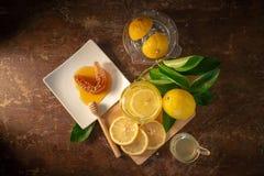 Χυμός λεμονιών με το μέλι στον ξύλινο πίνακα, τα λεμόνια και τα λογικά φύλλα στοκ εικόνα