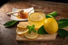 Χυμός λεμονιών με το μέλι στον ξύλινο πίνακα, τα λεμόνια και τα λογικά φύλλα στοκ εικόνες με δικαίωμα ελεύθερης χρήσης