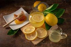 Χυμός λεμονιών με το μέλι στον ξύλινο πίνακα, τα λεμόνια και τα λογικά φύλλα στοκ εικόνες