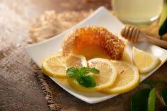 Χυμός λεμονιών με το μέλι στον ξύλινο πίνακα, τα λεμόνια και τα λογικά φύλλα στοκ φωτογραφίες με δικαίωμα ελεύθερης χρήσης