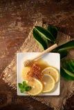 Χυμός λεμονιών με το μέλι στον ξύλινο πίνακα, τα λεμόνια και τα λογικά φύλλα στοκ φωτογραφία