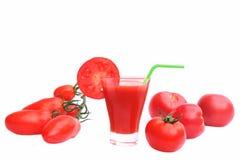 Χυμός ντοματών στο γυαλί και τις ώριμες ντομάτες Στοκ Φωτογραφίες