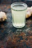 χυμός πιπεροριζών στο μικρό βάζο γυαλιού με τη ρίζα πιπεροριζών πίσω Στοκ εικόνα με δικαίωμα ελεύθερης χρήσης