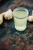 χυμός πιπεροριζών στο μικρό βάζο γυαλιού με τη ρίζα πιπεροριζών πίσω Στοκ φωτογραφία με δικαίωμα ελεύθερης χρήσης