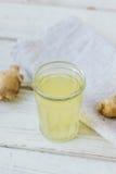 χυμός πιπεροριζών στο μικρό βάζο γυαλιού με τη ρίζα πιπεροριζών πίσω Στοκ εικόνες με δικαίωμα ελεύθερης χρήσης
