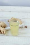 χυμός πιπεροριζών στο μικρό βάζο γυαλιού με τη ρίζα πιπεροριζών πίσω Στοκ Εικόνα