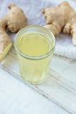 χυμός πιπεροριζών στο μικρό βάζο γυαλιού με τη ρίζα πιπεροριζών πίσω Στοκ Φωτογραφία