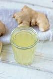 χυμός πιπεροριζών στο μικρό βάζο γυαλιού με τη ρίζα πιπεροριζών πίσω Στοκ Εικόνες