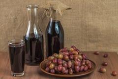 Χυμός σταφυλιών σε ένα γυαλί και στα μπουκάλια Στοκ εικόνες με δικαίωμα ελεύθερης χρήσης