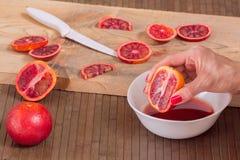 Χυμός συμπιέσεων χεριών από το πορτοκάλι αίματος Στοκ Φωτογραφία