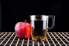 Χυμός της Apple και ένα κιβώτιο των κόκκινων μήλων Μαύρη ανασκόπηση Στοκ Εικόνες