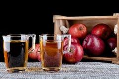 Χυμός της Apple και ένα κιβώτιο των κόκκινων μήλων Μαύρη ανασκόπηση Στοκ Εικόνα