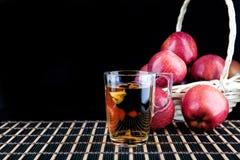 Χυμός της Apple και ένα κιβώτιο των κόκκινων μήλων Μαύρη ανασκόπηση Στοκ εικόνες με δικαίωμα ελεύθερης χρήσης