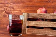 Χυμός της Apple και φρέσκα μήλα σε ένα ξύλινο κιβώτιο Στοκ Εικόνες