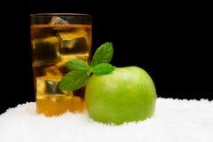 Χυμός της Apple, κύβοι πάγου και μήλο με τη μέντα στο Μαύρο στο χιόνι Στοκ φωτογραφία με δικαίωμα ελεύθερης χρήσης