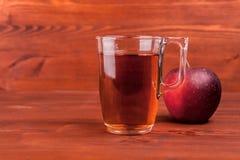 Χυμός της Apple σε ένα γυαλί και μήλα στο ξύλινο υπόβαθρο Στοκ Εικόνα