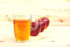 Χυμός της Apple σε ένα γυαλί και μήλα στο ξύλινο υπόβαθρο Στοκ Εικόνες