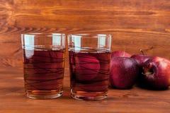 Χυμός της Apple σε ένα γυαλί και μήλα στο ξύλινο υπόβαθρο Στοκ εικόνες με δικαίωμα ελεύθερης χρήσης