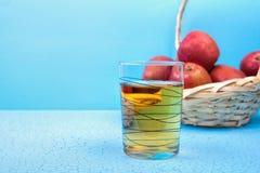 Χυμός της Apple σε ένα γυαλί και μήλα στο ξύλινο υπόβαθρο Στοκ εικόνα με δικαίωμα ελεύθερης χρήσης