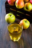 Χυμός της Apple σε ένα γυαλί και ώριμα μήλα σε έναν ξύλινο πίνακα Στοκ φωτογραφία με δικαίωμα ελεύθερης χρήσης