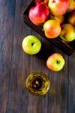 Χυμός της Apple σε ένα γυαλί και ώριμα μήλα σε έναν ξύλινο πίνακα Στοκ Εικόνες
