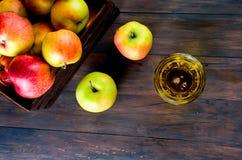 Χυμός της Apple σε ένα γυαλί και ώριμα μήλα σε έναν ξύλινο πίνακα Στοκ Φωτογραφίες