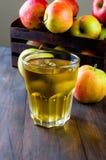 Χυμός της Apple σε ένα γυαλί και ώριμα μήλα σε έναν ξύλινο πίνακα Στοκ Φωτογραφία