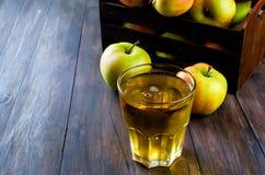 Χυμός της Apple σε ένα γυαλί και ώριμα μήλα σε έναν ξύλινο πίνακα Στοκ Εικόνα