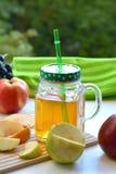 Χυμός της Apple σε μια κούπα και τα φρούτα Στοκ Εικόνες