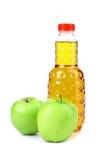 Χυμός της Apple σε πλαστικό μπουκάλι και δύο μήλα Στοκ Εικόνες