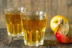 Χυμός της Apple στα γυαλιά και τα φρέσκα μήλα σε ένα ξύλινο υπόβαθρο Αγροτικό ύφος Στοκ Εικόνες