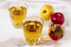 Χυμός της Apple στα γυαλιά και τα φρέσκα μήλα σε ένα ξύλινο υπόβαθρο Αγροτικό ύφος Στοκ εικόνες με δικαίωμα ελεύθερης χρήσης