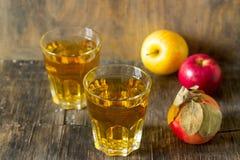 Χυμός της Apple στα γυαλιά και τα φρέσκα μήλα σε ένα ξύλινο υπόβαθρο Αγροτικό ύφος Στοκ φωτογραφία με δικαίωμα ελεύθερης χρήσης