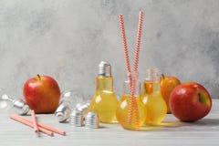 Χυμός της Apple στα χαριτωμένα βάζα λαμπών φωτός Στοκ Εικόνα