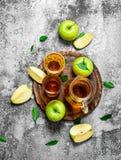 Χυμός της Apple στη στάμνα στην επιτροπή με φρέσκα, πράσινα μήλα Στοκ Εικόνες