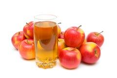 Χυμός της Apple στο γυαλί και ώριμα μήλα σε ένα άσπρο υπόβαθρο Στοκ εικόνα με δικαίωμα ελεύθερης χρήσης
