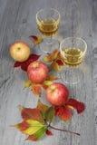 Χυμός της Apple, τρία μήλα και φύλλα φθινοπώρου Στοκ Εικόνα
