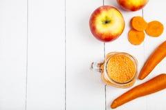 Χυμός Apple-καρότων σε έναν άσπρο ξύλινο πίνακα Στοκ Φωτογραφίες
