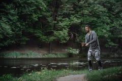 Χυτή ψαράς ράβδος αλιείας στη λίμνη ή το νερό ποταμού Άτομο με την περιστροφή του εξοπλισμού στον πράσινο δασικό υγιή τρόπο ζωής στοκ φωτογραφίες με δικαίωμα ελεύθερης χρήσης