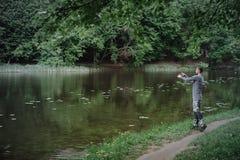 Χυτή ψαράς ράβδος αλιείας στη λίμνη ή το νερό ποταμού Άτομο με την περιστροφή του εξοπλισμού στον πράσινο δασικό υγιή τρόπο ζωής στοκ εικόνες