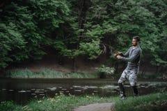 Χυτή ψαράς ράβδος αλιείας στη λίμνη ή το νερό ποταμού Άτομο με την περιστροφή του εξοπλισμού στον πράσινο δασικό υγιή τρόπο ζωής στοκ εικόνα με δικαίωμα ελεύθερης χρήσης