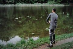 Χυτή ψαράς ράβδος αλιείας στη λίμνη ή το νερό ποταμού Άτομο με την περιστροφή του εξοπλισμού στον πράσινο δασικό υγιή τρόπο ζωής στοκ εικόνες με δικαίωμα ελεύθερης χρήσης