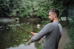 Χυτή ψαράς ράβδος αλιείας στη λίμνη ή το νερό ποταμού Άτομο με την περιστροφή του εξοπλισμού στον πράσινο δασικό υγιή τρόπο ζωής στοκ εικόνα