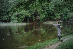 Χυτή ψαράς ράβδος αλιείας στη λίμνη ή το νερό ποταμού Άτομο με την περιστροφή του εξοπλισμού στον πράσινο δασικό υγιή τρόπο ζωής στοκ φωτογραφία