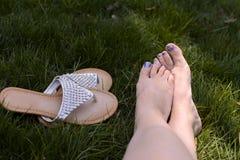Χωρίς παπούτσια χαλαρώνοντας στη χλόη Στοκ Φωτογραφία