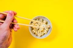 Χωρίστε σε τετράγωνα στο άσπρο κύπελλο με chopsticks στο κίτρινο υπόβαθρο στοκ φωτογραφίες