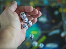 Χωρίστε σε τετράγωνα την πτώση από το χέρι του σε έναν ζωηρόχρωμο πίνακα παιχνιδιών Στοκ Εικόνες