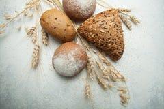 Χωριάτικες μαύρες ψωμί και σίκαλη με το σίτο σε έναν παλαιό παλαιό άσπρο πίνακα Χρυσά spikelets μεταξύ του ψωμιού στοκ εικόνες με δικαίωμα ελεύθερης χρήσης