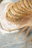Χωριάτικοι ψωμί και σίτος σε έναν παλαιό εκλεκτής ποιότητας γκρίζο ξύλινο πίνακα Στοκ φωτογραφία με δικαίωμα ελεύθερης χρήσης